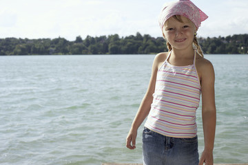 Little girl with bandana in front of a lake