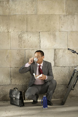 Businessman drinking coffee in crouched position