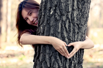 woman hands making a heart shape around a big tree as love nature concept in vintage color tone