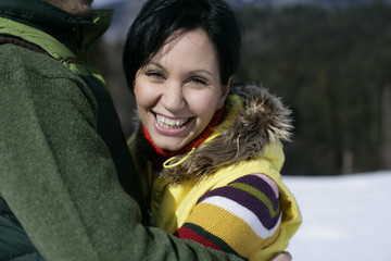 Couple embracing each other, young woman smiling at camera