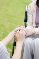 Caretaker and mature woman on wheelchair holding hands
