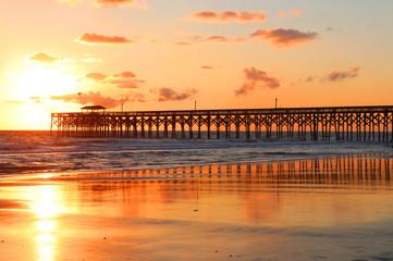 Atlantic ocean sunrise background. Golden sunrise over the ocean. Atlantic ocean landscape with a wooden pier in Myrtle Beach area, South Carolina, USA.