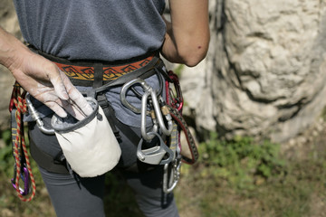 Young man with a harness and a chalk bag is standing in front of a rocky wall (part of), close-up