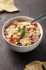 Chicken Tortilla Soup on wooden background with chips with spoon