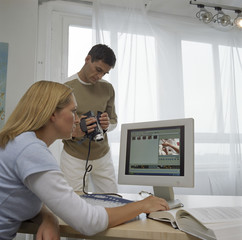 Blond woman and brunette man sitting in front of a computer - Filming - Studio