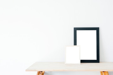 Mockup frame photo on wooden table, Frame on white wooden table, put walls white background.
