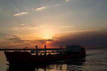 танкер идет по реке на закате