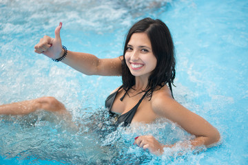 Close-up portrait of smiling girl enjoying in jacuzzi and showing thumb up gesture of good class in the pool at the resort