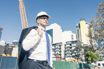 Senior elegant builder man in suit at construction site on sunny