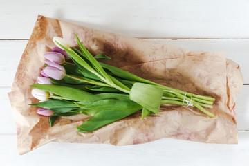 Blumenstrauß mit weißen und violetten Tulpen auf weißem Holz