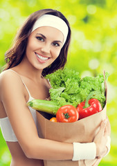 smiling woman in fitness wear with vegetarian food
