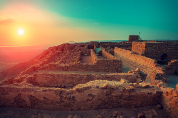 Zelfklevend Fotobehang Diepbruine Beautiful sunrise over Masada fortress. Ruins of King Herod's palace in Judaean Desert.