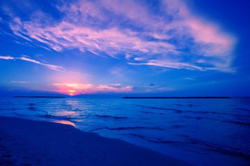Early morning, sunrise over sea. Blue pink beautiful sunrise. Twilight time on the beach.