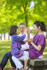Girl and mother playing clapping games beside grandfather on park bench