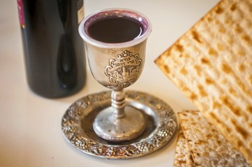 """Red wine, a cup full of wine with the text of the traditional wine blessing """"Borei Pri HaGafen"""" (""""Blessed is the fruit of vine"""") and matzot. Passover seder set stock image blurred. Israel, April 2016."""