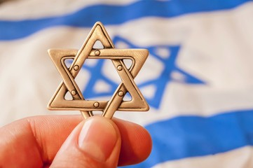 Fingers holding a Jewish star hexagram with Israeli flag on the background. Zionism, giyur, Judaism conversion concept. Israeli citizenship, Israel Independence Day, Yom Haatzmaut, Yom hazikaron.