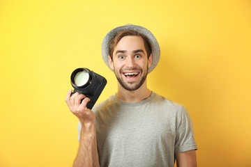 Handsome young photographer on color background