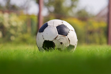 Old Soccer ball on a green grass. Football on a sports field. Sunny day. Summer time. Sporting goods. Closeup
