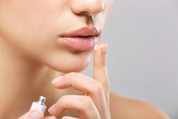 Beautiful woman applying cream onto lips on light background