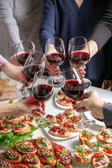 People clinking glasses with wine and delicious dishes on table