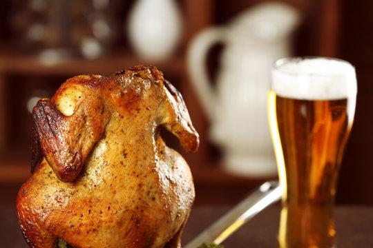 Grilled beer can chicken on blurred background