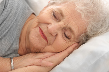 Elderly woman sleeping in bed