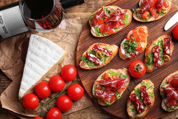 Tasty bruschetta served with wine on wooden background