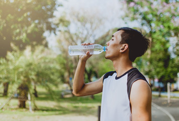 Sports man drinking water after exercising on background of green trees.