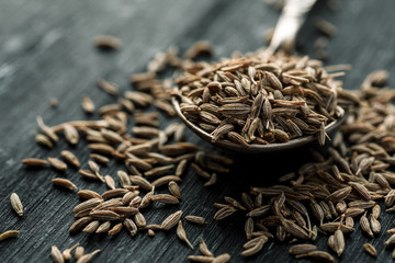 Cumin seeds in metal spoon on a wooden table, horizontal, selective focus