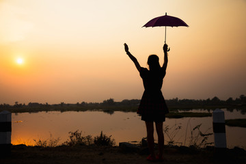 silhouette of girls raising an umbrella to sky at sunset by lake