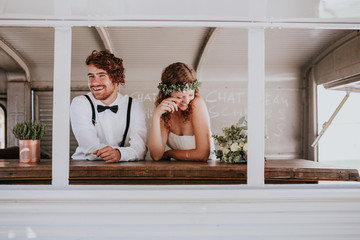 bride and groom laughing in a waggon