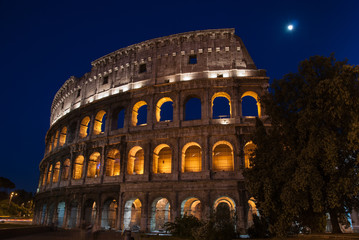 Colosseum in Rome, Italy, illuminated at night with moon shining above