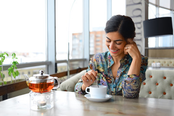 cute girl with braces smiling, sitting in a cafe with a Cup of tea