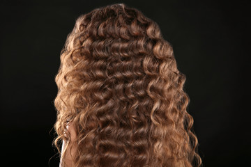 Healthy hair. Curly long hairstyle. Back view of Brown hairs. hair styling isolated on black studio background.