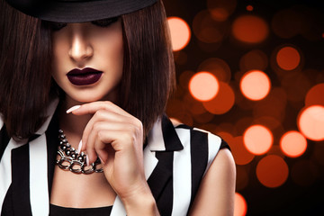 Fashion photo of beautiful young lady in black hat on bokeh lights background. Perfect face makeup.