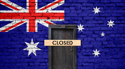 Australia flag on brick wall with closed door and Closed sign
