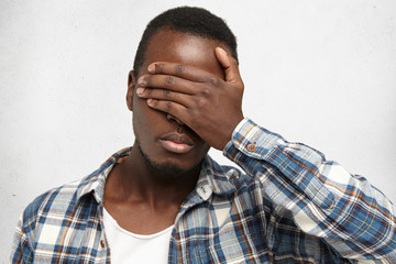 Human face expressions, emotions and feelings. Young African American man wearing checkered shirt over white t-shirt, covering face with hand, feeling sorry or ashamed, doesn't want to show his eyes