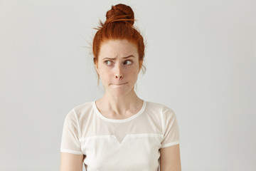 Indoor shot of cute redhead girl looking away, having doubtful and indecisive face expression, pursuing her lips as if forbidden to say anything. Confused young female posing isolated at white wall Fototapete
