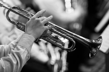 Hands of man playing the trumpet in the orchestra in black and white