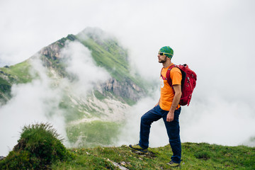 Young sports guy with a backpack hiking in green mountains in Romania