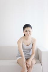 Woman sitting on sofa massaging leg