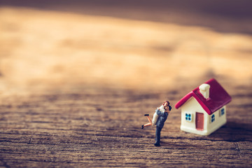 miniature couple and miniature house with red roof on wooden mock up on day noon light.Image for property real estate investment concept.  Image for Love couple concept.