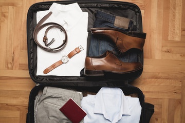 Open traveler's bag with men clothing, accessories, wallet, leather shoes, passport and watch. Travel and vacations concept.