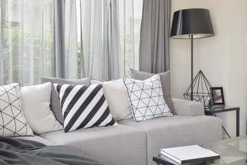 Varies pattern pillows in monotone setting on light gray sofa with black standing lamp