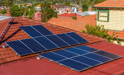 Solar panels on a red roof in a suburban setting in Australia