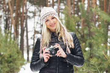 Young attractive blonde woman with an old camera