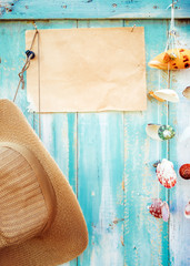 Summer background - Blank old paper and straw hat with shell decoration hanging on wood wall background.  vintage color tone styles.