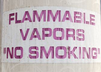 Old faded FLAMMABLE VAPORS NO SMOKING sign.