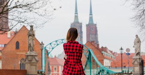 beautiful young woman hugging herself in front of the splendid view of church in Poland