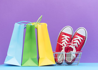 red gumshoes in shopping cart and shopping bags on the wonderful purple background